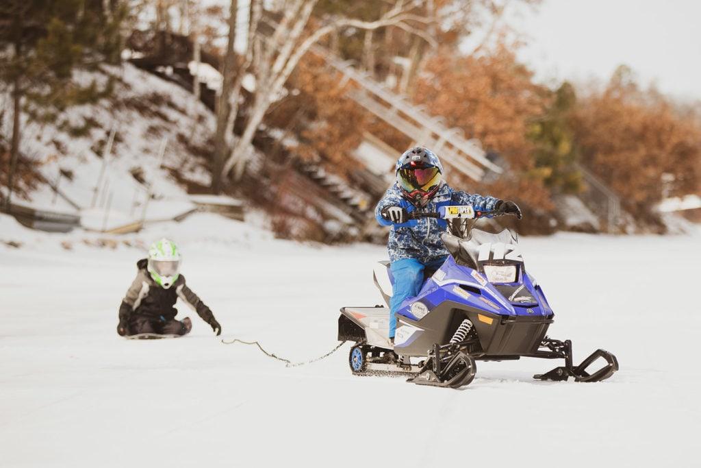 snowmobile pulling kid on sled