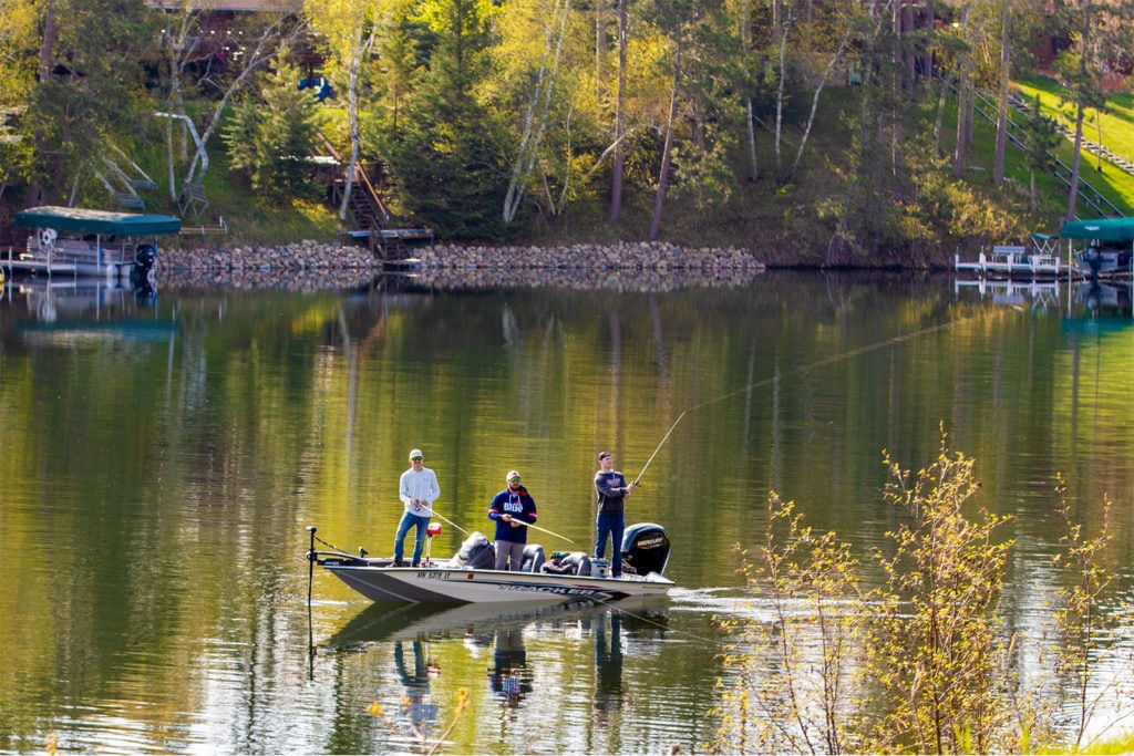 Three men fishing off of a boat on a lake