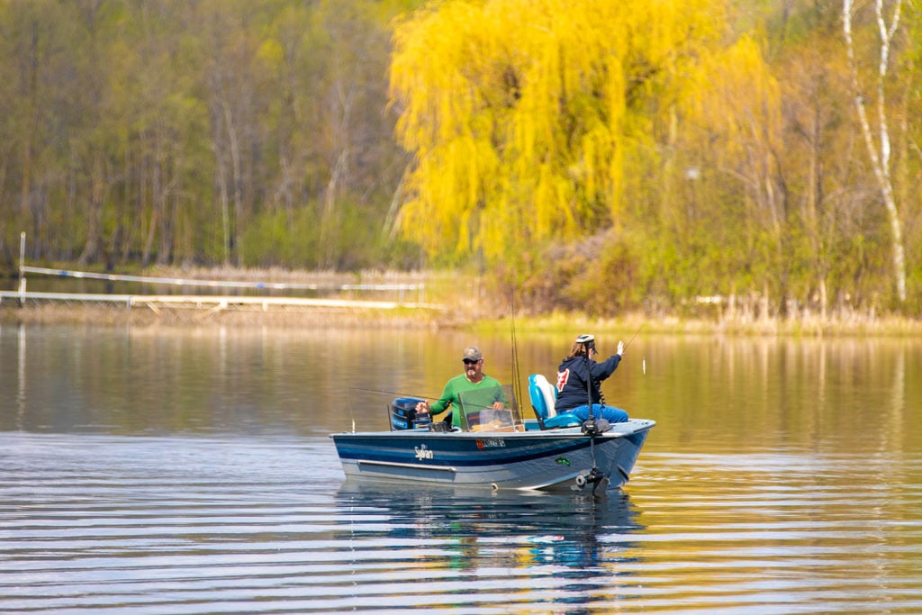 Two people fish on a speedboat